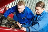two motor mechanic engineers examining timing belt and internal combustion engine of automobile car