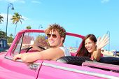 Couple happy in vintage retro convertible car. Friends driving on summer road trip in pink car. Beautiful young Caucasian man and Asian woman smiling joyful on sunny summer day traveling.