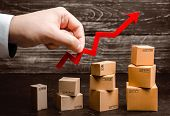 Businessman Holds A Red Arrow Up Above Cardboard Boxes Folded Incrementally. Increase Sales And Prod poster