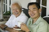 stock photo of early 60s  - Father and Son Drinking Coffee - JPG