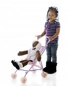 A happy preschooler stopping to pose with the doll she's pushing in an umbrella stroller.  On a whit