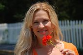 Attractive, Young, Blond Woman Holding A Red Flower