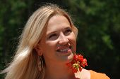 Attractive, Young, Blond Woman Holding A Red Geranium