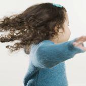 Young Hispanic girl spinning around