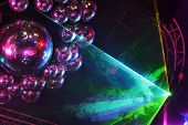 Beautiful shiny balls and colorful rays on ceiling in night club