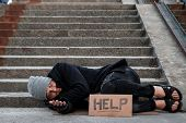 A Man, Homeless, A Man Sleeping On A Cold Floor In The Street With A Help Sign. Concept Of A Homeles poster