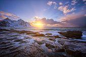 Beach of Norwegian sea on rocky coast in fjord on sunset in winter. Vareid beach, Lofoten islands, N poster