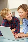 Mother and son using laptop in domestic kitchen poster