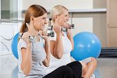 Two happy senior women using dumbbells for exercise in gym