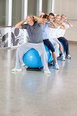 Senior citizens doing back exercises on gym ball in gym