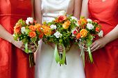 three wedding bouquets being held by a bride and her bridesmaids