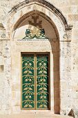 Entrance to the Coptic Church of the Holy Sepulchre in Ierusalime.Green doors are decorated by gold