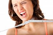 Dieting - young woman is choking herself literally with measuring tape