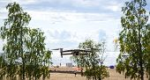Modern Drone Hovering In Nature On The Seashore Over The Beach And Blue Sky poster