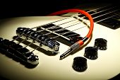 stock photo of cord  - Detail on an electrical guitar and a red cord - JPG