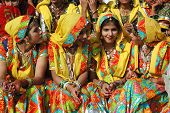 Beautiful indian women in traditional rajasthani clothes preparing to dance at camel fair