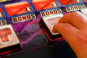 foto of coin slot  - gambler playing a gaming machine at the amusement arcade - JPG