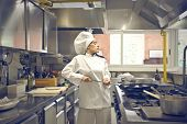 young woman chef with frying pan in the kitchen