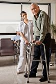 Portrait of senior man being assisted by female nurse to walk Zimmer frame with person sitting in ba