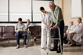 Senior man being helped by female nurse to walk the Zimmer frame with people sitting in hospital lobby