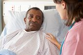 foto of geriatric  - Nurse Talking To Senior Male Patient On Ward - JPG