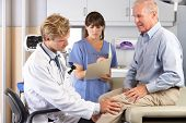 stock photo of knee  - Doctor Examining Male Patient With Knee Pain - JPG