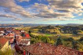 View on red tiled roofs of small town among hills and meadows under beautiful sky at sunset in autum