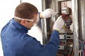 stock photo of electrician  - Electrician checking fuse box using a digital multimeter - JPG