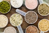 scoops of superfood - healthy seeds and powders (white and brown chia, brown and golden flax, hemp, pomegranate fruit powder, wheatgrass, hemp and whey protein, maca root) - top view
