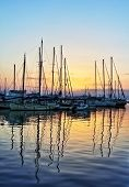 The sun sets behind the yachts in the harbour at Aegina, Greece, their reflections distorted by ripples on the water