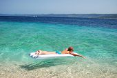 teenage boy swimming on a mattress in adriatic waters