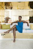 Full length of happy African American woman sitting crossed legs in a lavish store