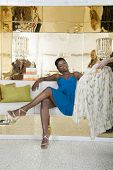 An elegant African American woman considering apparel presented by personal shopper
