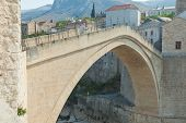 MOSTAR, BOSNIA - AUGUST 10: Man climbing the old Mostar bridge on August 10, 2012 in Mostar, Bosnia. The old bridge is a reconstruction of a 16th century Ottoman bridge in the city of Mostar.