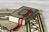 stock photo of quran  - The Quran and the prayer beads on a carpet - JPG