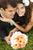 wedding, beautiful young bride lying together with groom in love on green grass kissing, park summer outdoor