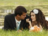 wedding, beautiful young bride lying together with groom in love on green grass, park summer outdoor