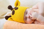 cute sleeping baby boy in funny hand made giraffe hat, beautiful kid dozing on plaid, studio shot