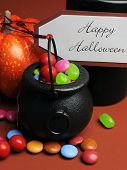 Halloween Trick Or Treat Witches Cauldrons Full Of Candy On Autumn Brown Background With Black Candl