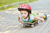 Little girl in protective helmet lies on skateboard looking ahead, arms along body.