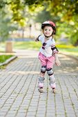Little girl in protective equipment roller-skates on walkway in park