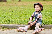 Little girl in protective equipment and rollers sits resting on curb of walkway in park