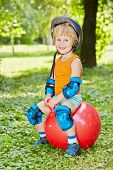 Smiling little boy in protective equipment sits on red ball for jumping on lawn in park