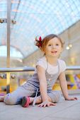 Little cute girl sits on floor and admiringly looks into distance in mall.
