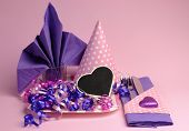 Pink And Purple Theme Party Table Setting Decorations, Against A Pale Pink Background..