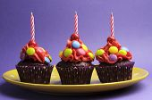 Three Bright Candy Covered Cupcakes With Birthday Candles On Yellow Polka Dot Plate Against A Purple