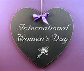 International Women's Day Message Written On Heart Shape Blackboard Sign Against A Purple Background