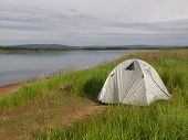 White camping tent at a river