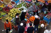 People buy and sell fruit at open air market