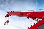 image of crane hook  - Red truck crane boom with hooks and scale weight above blue sky - JPG